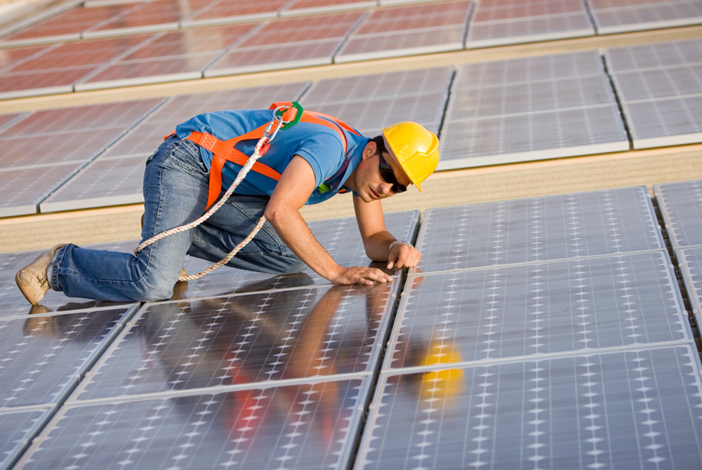 Solar job trainees installing solar panels on a roof