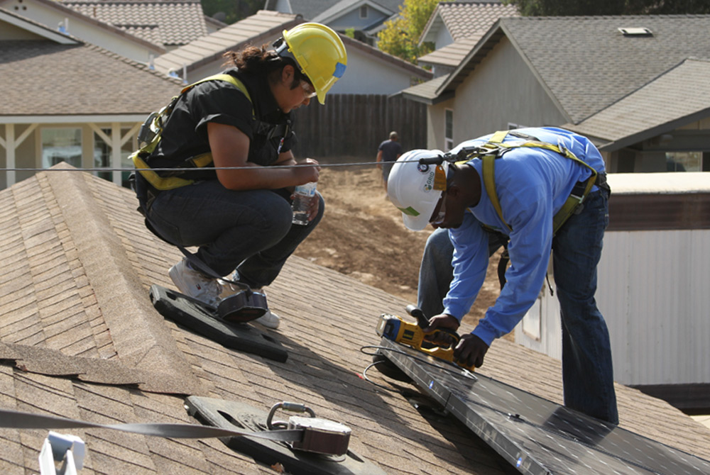 Solar contractors training potential job candidates on rooftop energy system installation