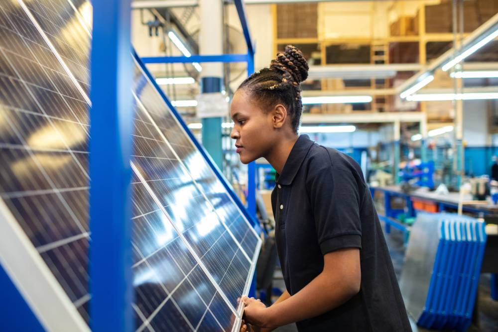 Woman inspecting a solar panel in a factory