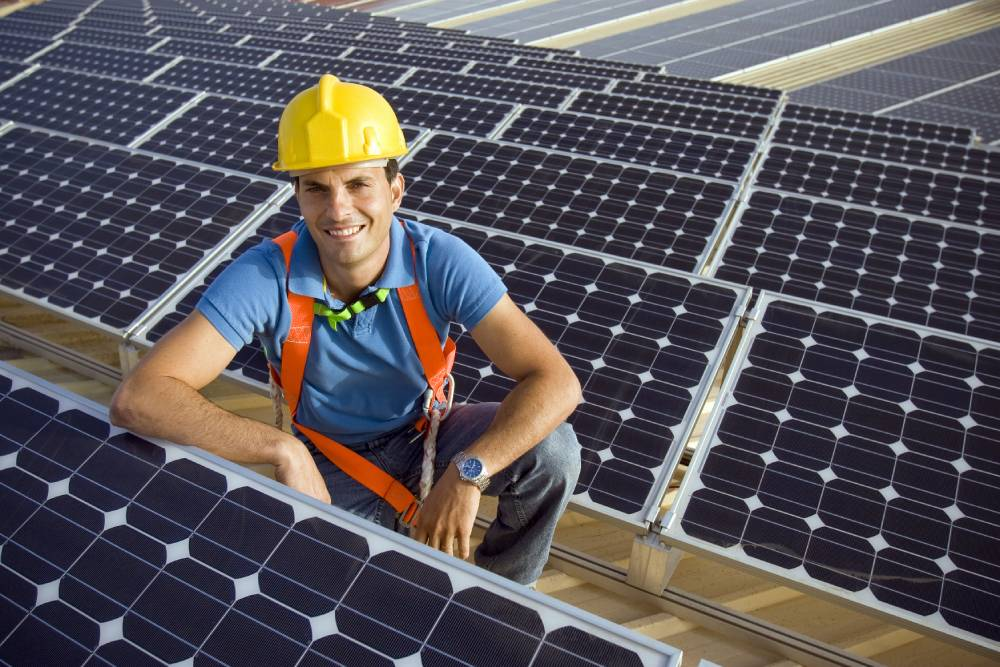 Solar contractor sitting next to solar panels array